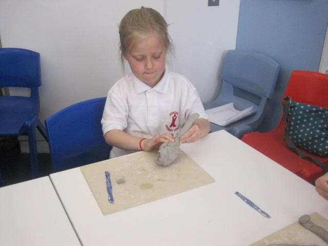 Building our dinosaur designs with clay