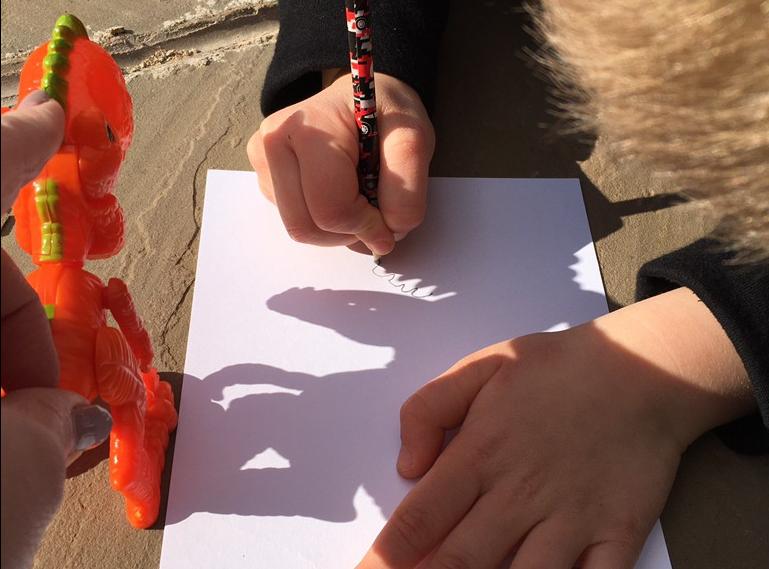 Drawing dinosaur shadows.
