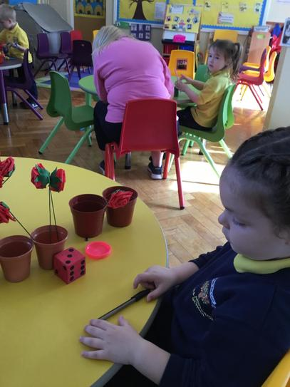 Emily is rolling a dice and planting the same number of flowers