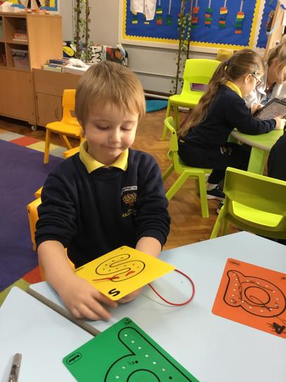 "Calvin is really concentrating to make the letter ""s"" using string."