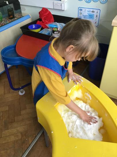 Olivia exploring foam in the sensory tray.