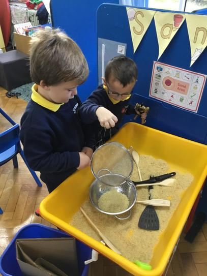 Sam and Jack loved the rice in the sand tray.