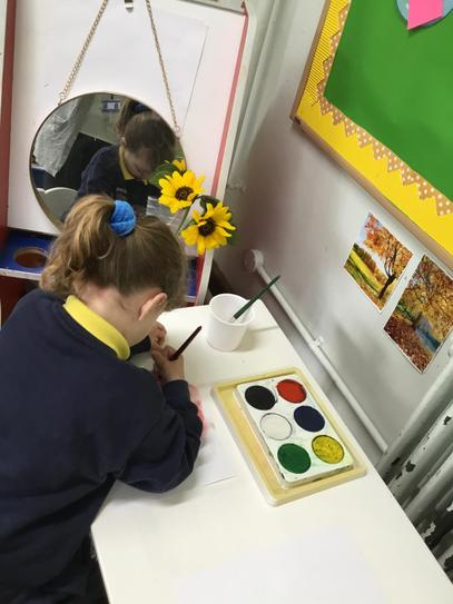 Look at the concentration as Hollie paints the sunflowers.