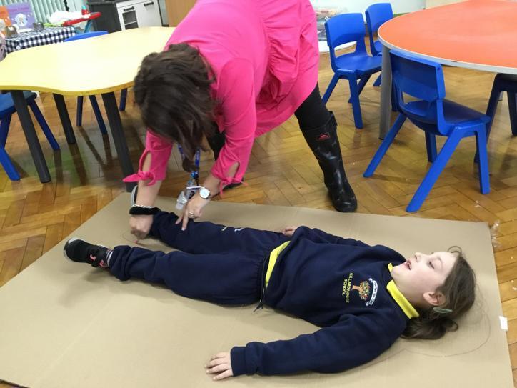 Mrs Caughey is drawing around Adrianna's body ~ we will paint it next week!