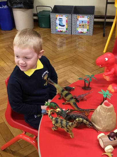 Euan is enjoying playing with the dinosaurs.