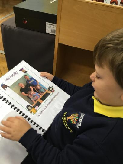Sam loves to look through his 'All about me book'. You have a lovely family Sam.