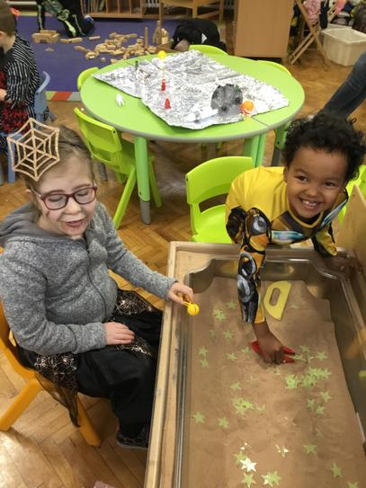 Amelia and Nathanael are catching stars in the sand tray