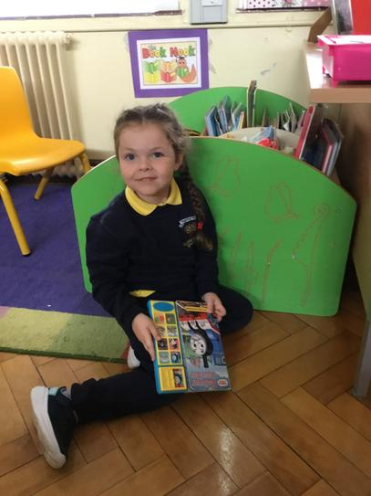 Emily loves to read in the story corner.