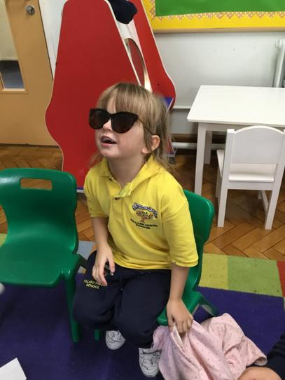 Olivia having a turn wearing Mrs C's sunglasses.