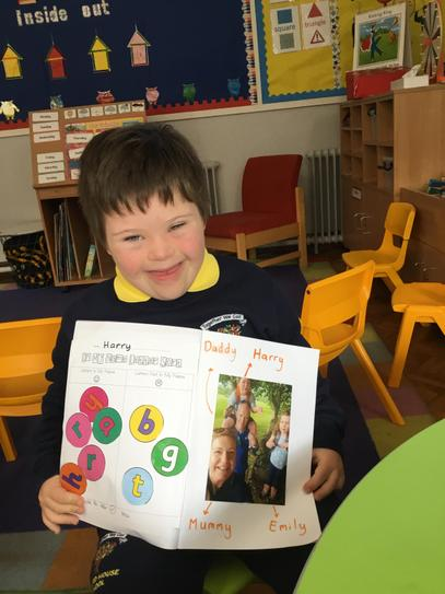 Harry labelled a family photo and traced over the letters in literacy.