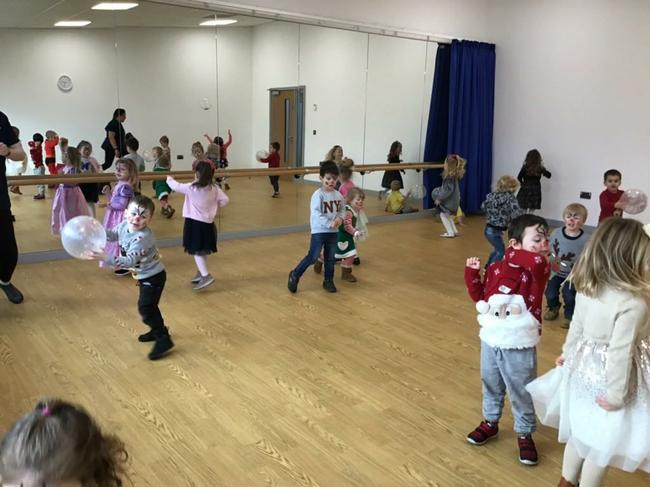 The children dance to Christmas songs.