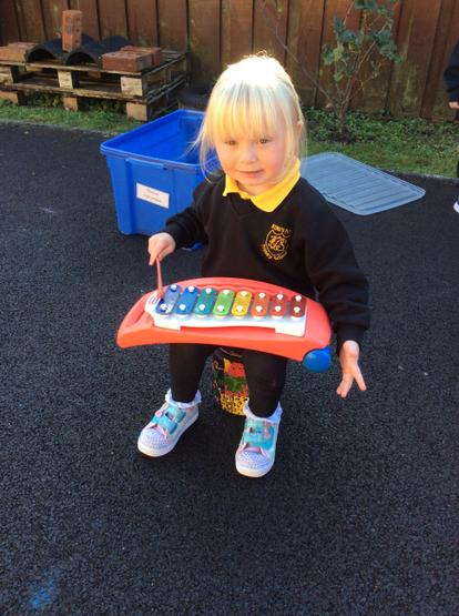 Using a beater to play the xylophone.
