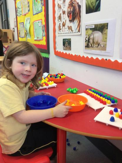 Using small pegs to develop fine motor skills.