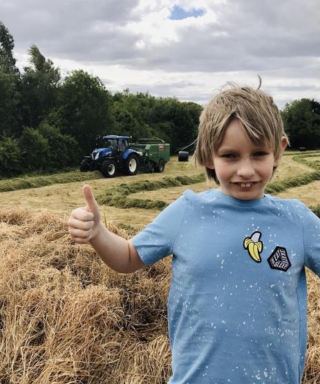 Seth P5Gl watches the farmer make hay bales