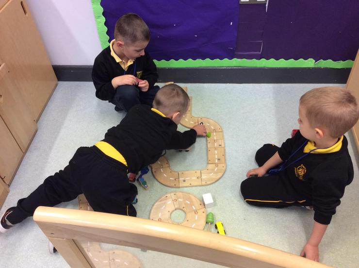 Building a wooden road with friends on the floor area.