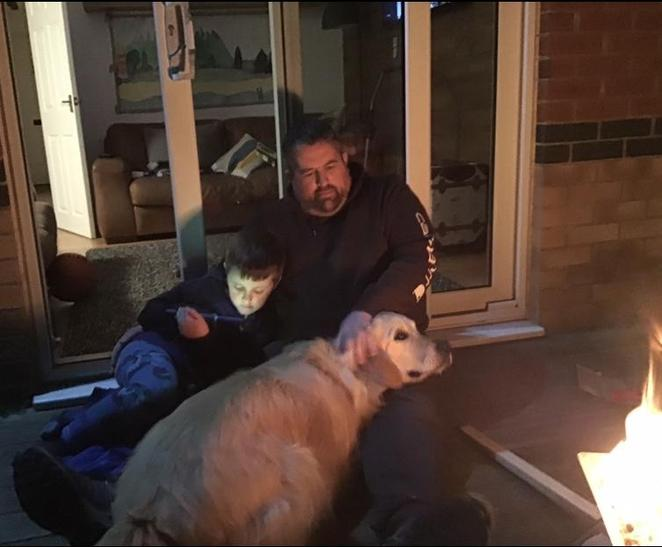 Beau, his daddy and his dog sat by a campfire.