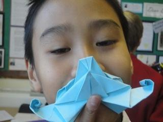 Trying on the origami clocks moustache