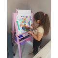 Leila painting a beautiful picture on her easel.