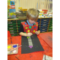 Using collage and paint to create rocket pictures.