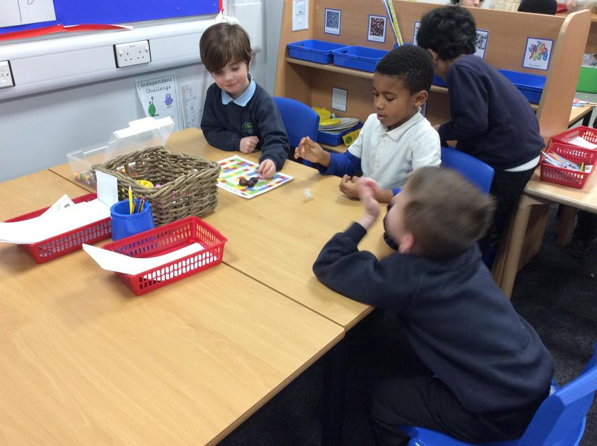 The boys working collaboratively in the maths area