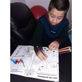 Aqib working hard on his dinosaur activity book!