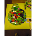 transient art.  We used our pincer grip to pick up the pompoms and decorate the bauble