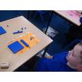 Making 3-digit numbers using concrete apparatus.