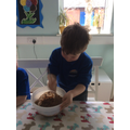 Mixing shredded wheat into the chocolate.