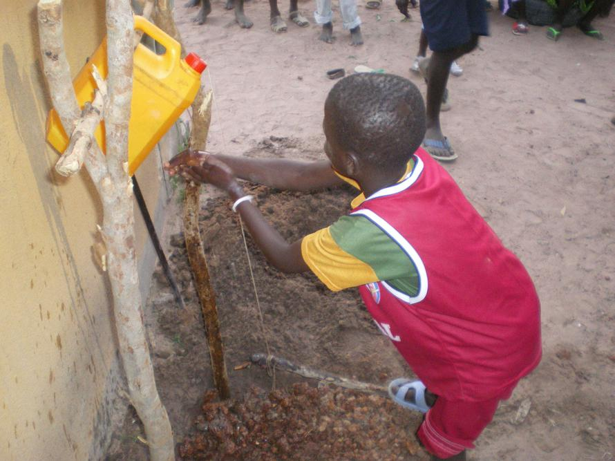 Gambian child using a tippy tap