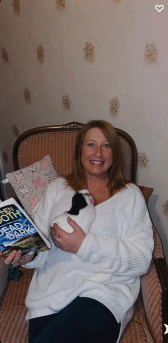 Mrs Guest, a year 3 teacher who loves to read when cuddling her guinea pig
