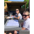 Jack and his sister doing maths in the sun