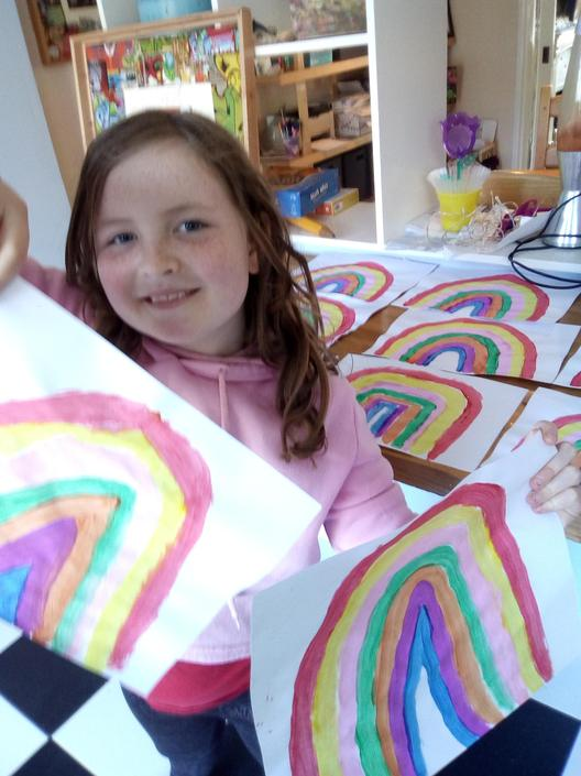 Poppy painting rainbows for her neighbours!