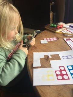Using the scissors to practise cutting skills. Cutting out the Numicon pieces.