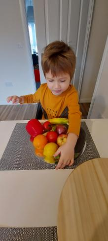 Kacper making a rainbow out of fruit.