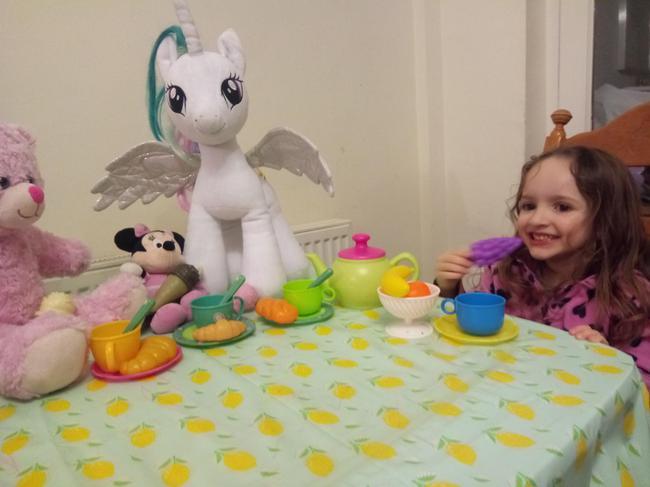 Sofia enjoying a snack with her teddy bears.