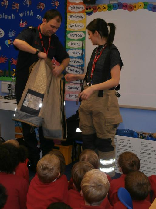 The Firefighter helped her to put on the tunic