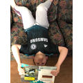 C reading upside down on the sofa
