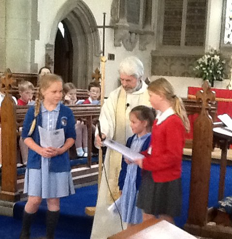 Receiving rhe Cross of Nails from Barford Primary