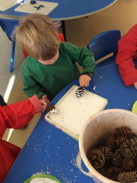 Making wintery fir cones with glue, glitter and snow.