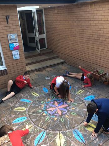 Students creating a welcoming Chalk Mandala outside
