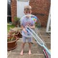 George enjoyed catching bubbles outside.
