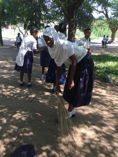 Some children sweep the school grounds.