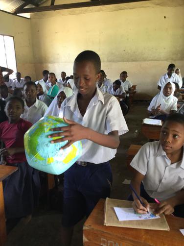 The children enjoying learning using a globe