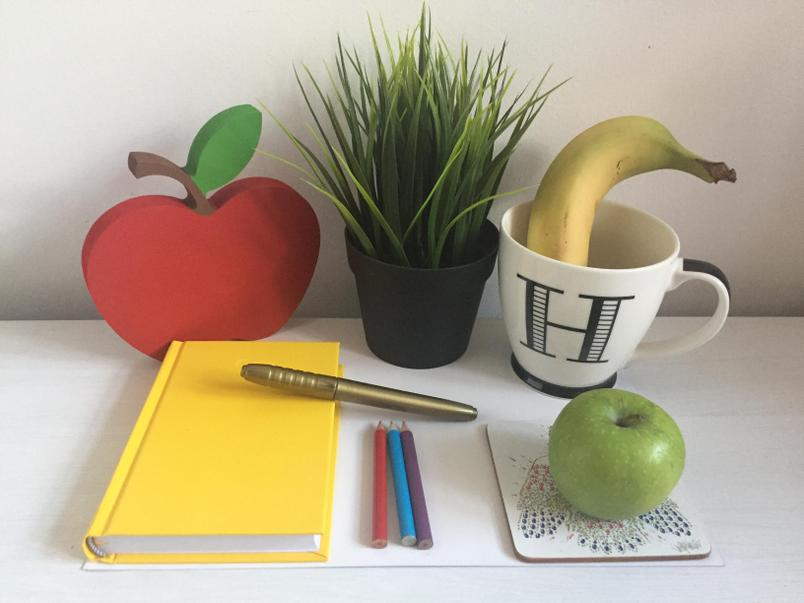 Example: The red apple is behind the yellow book.
