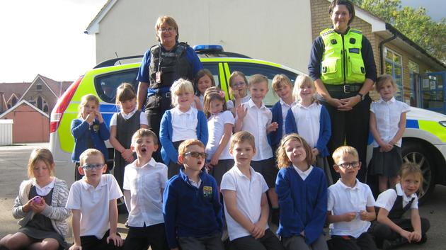 A class photo in front of the police car.
