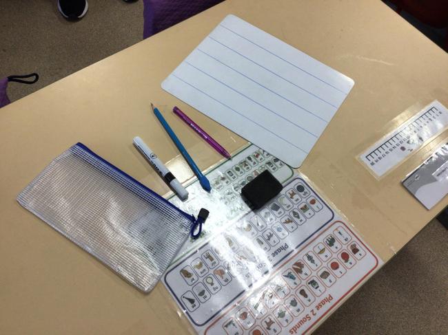 A pencil case with a white board pen, white board rubber, pencil and rubber.