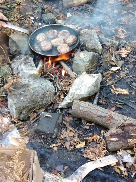 Cooking burgers over an open fire at forest school