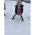 Reception children practising writing red words in the snow at school.