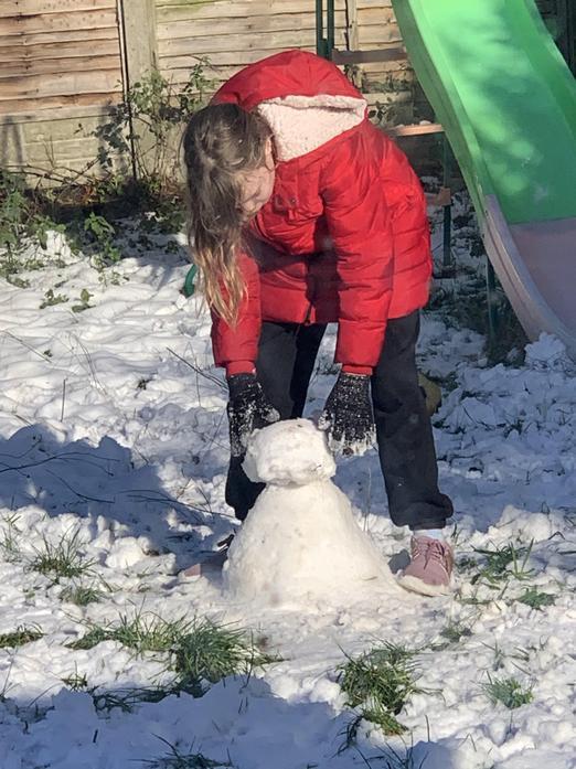 Felicity builds a snowman.