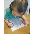 Isabel is showing good concentration when tracing numbers